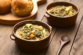 stock photo of legume  - Vegetarian soup made of lentils spinach potato carrot and onion served in dark brown bowls with buns in the back  - JPG