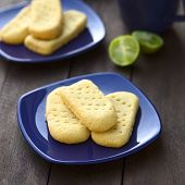 stock photo of shortbread  - Homebaked shortbread biscuits on small plates with cup of tea in the back  - JPG