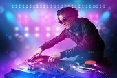 stock photo of disc jockey  - Young disc jockey mixing music on turntables on stage with lights and stroboscopes - JPG
