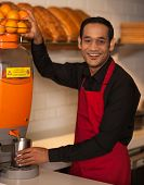 picture of juicer  - Young happy indian chef with juicer machine - JPG