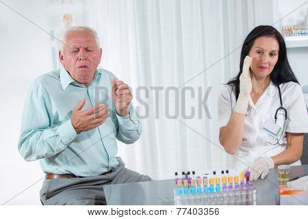Elderly patient coughs into the doctor's office