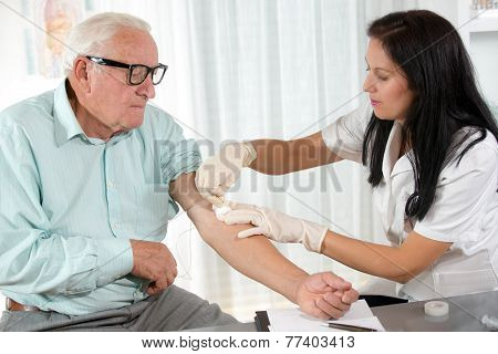 Nurse with syringe is taking blood for test at the doctor office