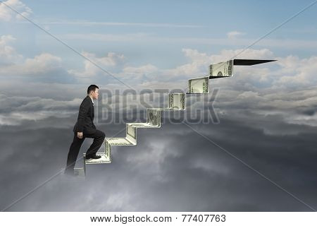 Businessman Climbing On Money Stairs With Natural Sky Cloudscape