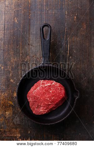 Raw Meat Ribeye Steak On Cast Iron Frying Pan On Dark Wooden Background