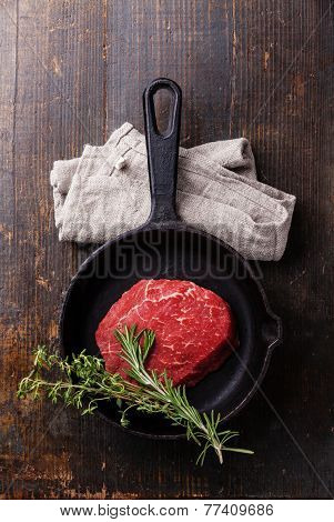 Raw Meat Ribeye Steak And Spicy Herbs On Cast Iron Frying Pan On Wooden Background