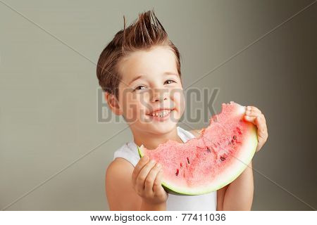 Happy four years old boy smiling with watermelon