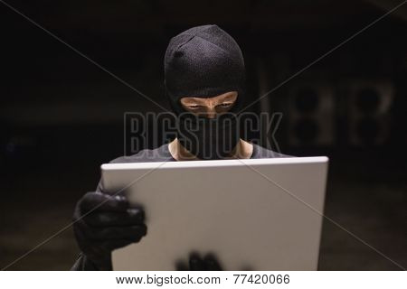 Hacker using laptop to steal identity on shadowy background