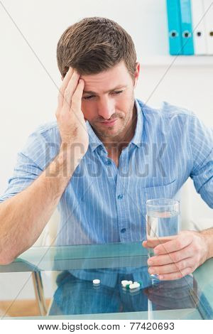 Hungover businessman holding glass of water and tablet in his office