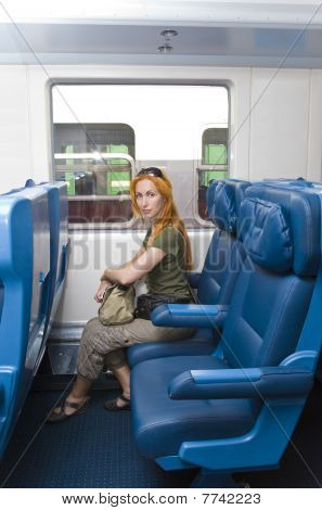 Interior of a passenger train with young woman sitting into the railway car