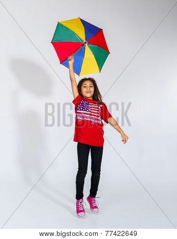 Cute Little Smiling Afro-american Girl Jumping With Colorful Umbrella