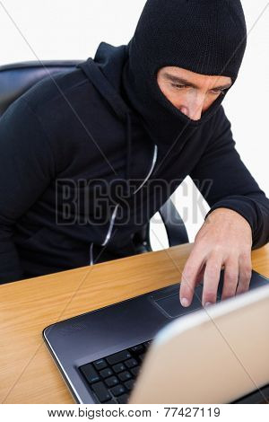 Thief with balaclava hacking a laptop on white background