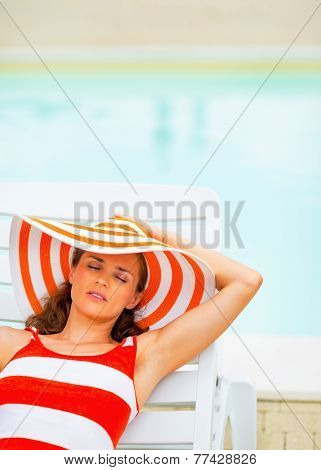 Portrait Of Relaxed Young Woman In Hat Sitting Laying On Chaise-