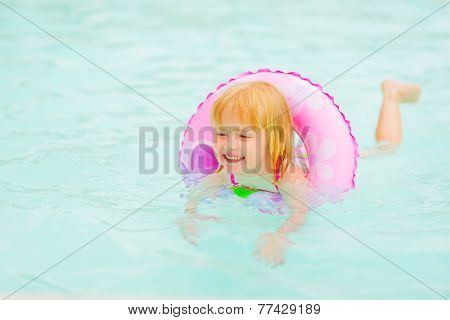 Happy Baby Girl With Swim Ring Swimming In Pool