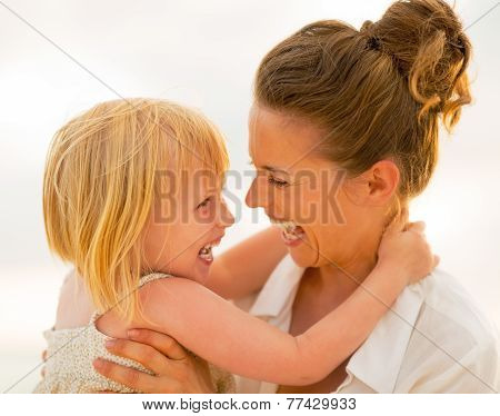Portrait Of Smiling Mother And Baby Girl Hugging On Beach At The