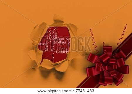 Red christmas bow and ribbon against circle hole in paper