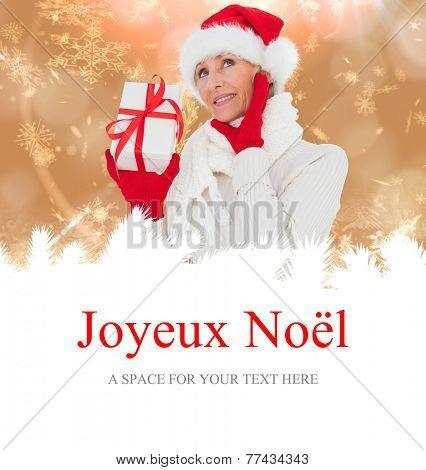 festive woman holding gift against joyeux noel