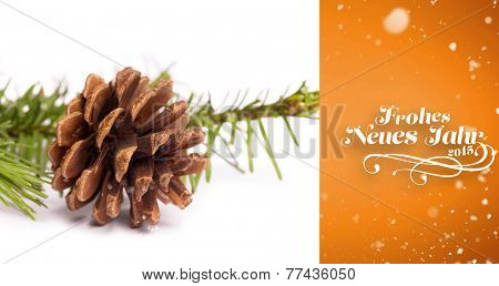Snow falling against brown pine cone with fir branch