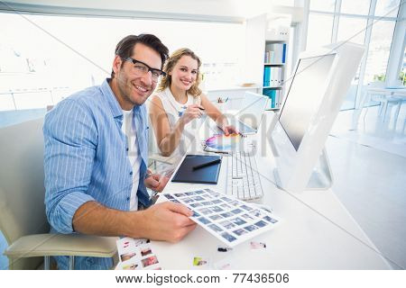Two happy photo editors working with contact sheets in office