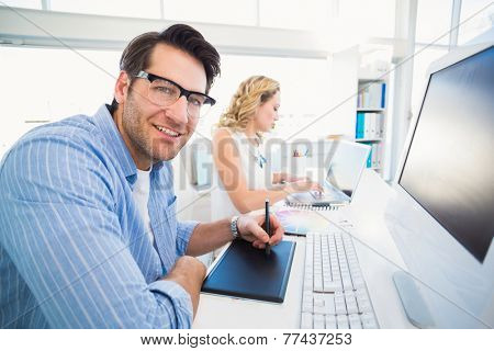 Designer using a graphics tablet while looking at camera in office