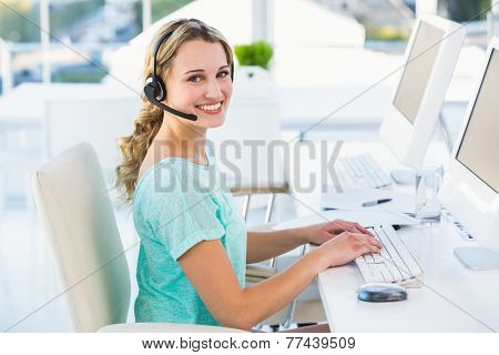 Pretty call centre agent sitting at her desk on a call in the office