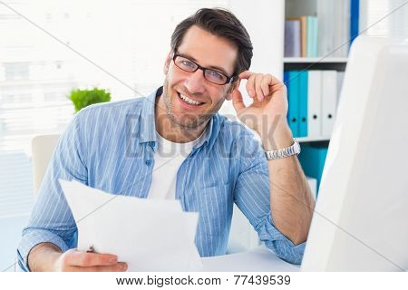 Smiling photo editor at work holding contact sheet in office