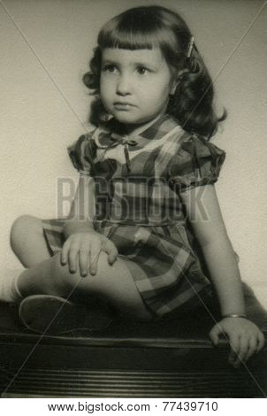 CANADA - CIRCA 1950s: An antique photo shows portrait of a little brunette girl in a plaid dress