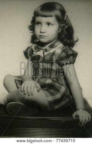 CANADA - CIRCA 1950s: An antique photo shows portrait of a little brunette girl in a plaid dress