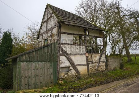 Rundown timbered house on a mound at fall