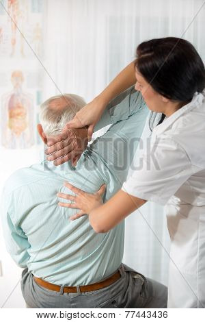 Chiropractic: Chiropractor examining senior man at office