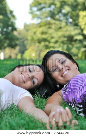 Two Friends Lying Outdoors In Grass Holding Hands