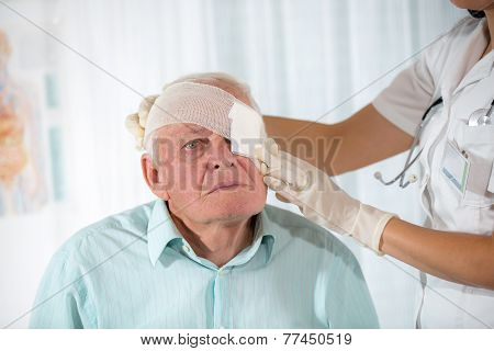 Nurse bandaging older man eyes