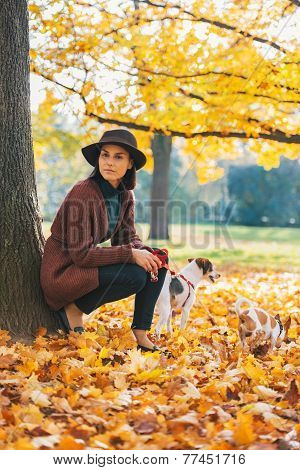 Young Woman With Dog Standing Outdoors In Park In Autumn