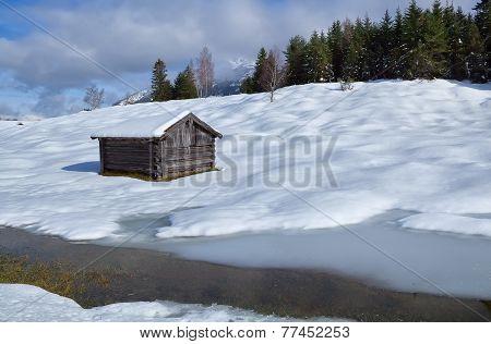 Old Wooden Hut On Snowy Alpine Meadow
