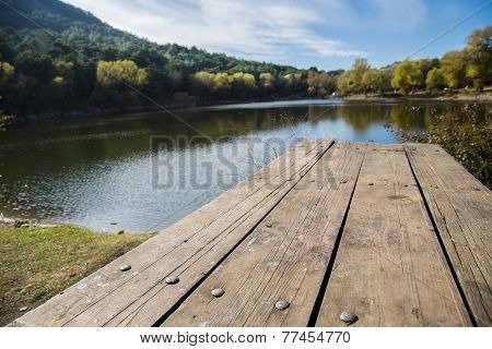 Perspective Of Wooden Picnic Table With Blur Landscape Background