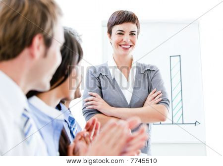 Portrait Of A Smiling Businesswoman Talking At Her Colleague During A Meeting