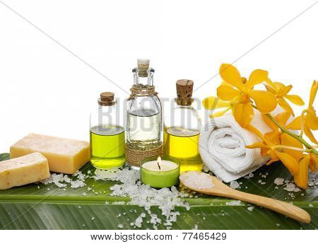 spa supplies with orchid, oil, yellow candle ,soap ,salt ,towel on banana leaf