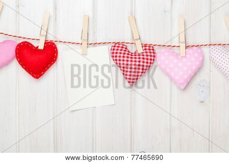 Photo frame and valentines day toy hearts over white wooden background