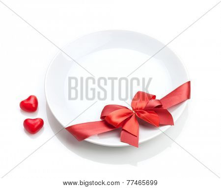 Valentine's Day heart shaped candy and plate with red bow. Isolated on white background