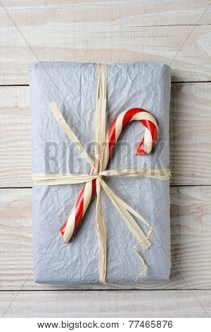 High angle shot of an old fashioned Christmas present. The gift is wrapped in crumpled tissue paper and tied with raffia. A large candy cane is on top of the present.