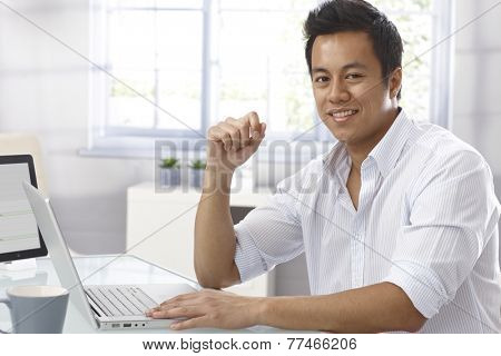 Portrait of happy young Asian businessman sitting at desk, working with laptop computer, looking at camera.