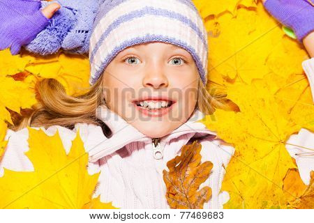 Close-up portrait girl lay in autumn maple leaves