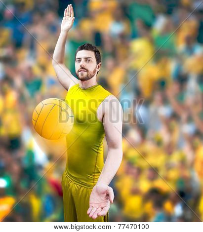 Volleyball player on yellow uniform on volleyball court.