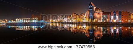 Panorama of Gdansk old town at night with reflection in Motlawa river, Poland