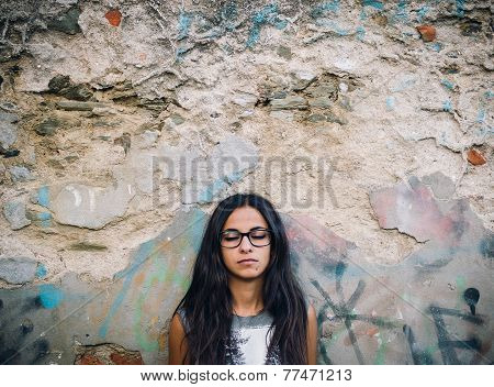 Young Woman With Eyes Closed Over A Wall Background Outdoors