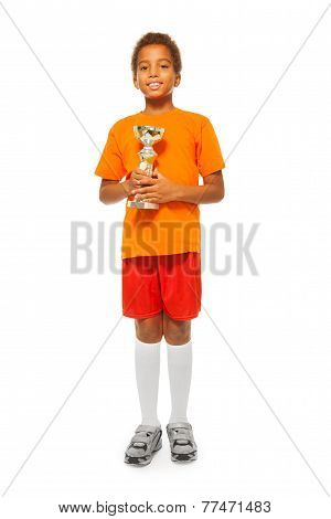 Little African boy with prize cup in sport game