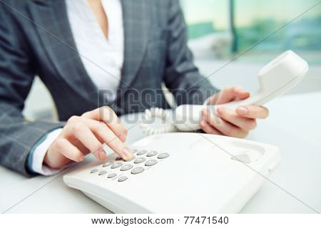 Businesswoman dialing telephone number