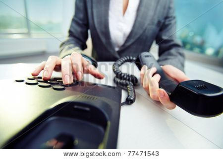 Businesswoman holding phone receiver and dialing number