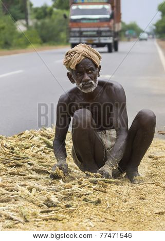 Old Dark-skinned Farmer Works His Mellet On Public Road.
