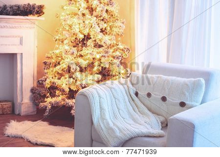 Beautiful holiday decorated room with Christmas tree and white comfortable chair with soft knitted blanket and cushion on it