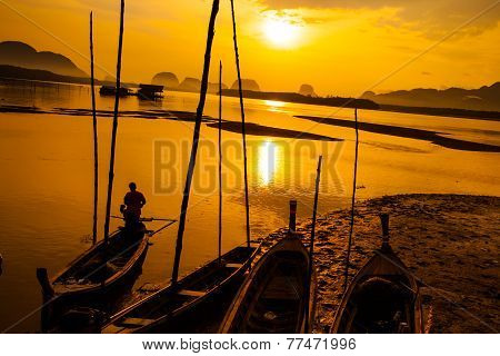 Silhouette of fisherman and traditional thai boats at Sam chong Tai Phangnga province.